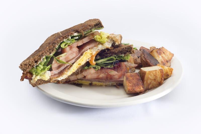 Schinkeneitomatenfrühstücks-Sandwichbratkartoffeln stockbilder