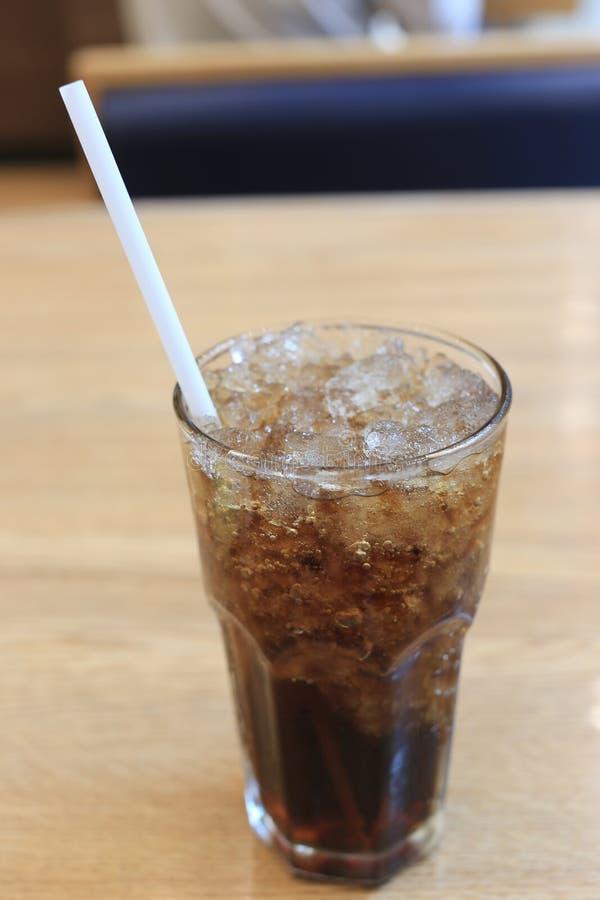 Schiocchi il vetro della soda con ghiaccio e un tubo fotografia stock libera da diritti