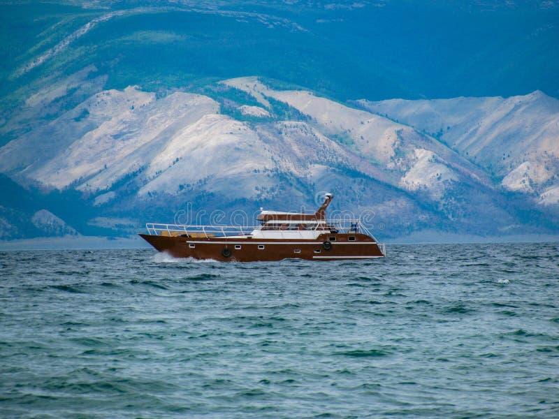 Schip in de wateren van meer Baikal op de achtergrond van heuvels stock afbeeldingen