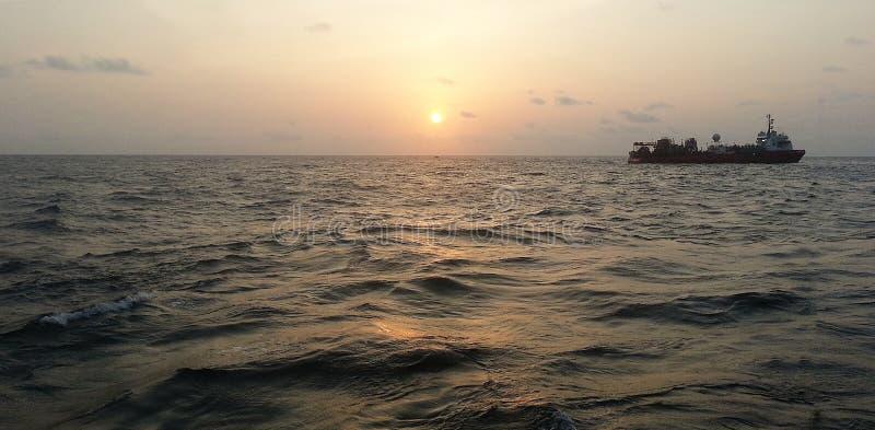 Schip op de oceaan tijdens zonsondergang royalty-vrije stock afbeelding