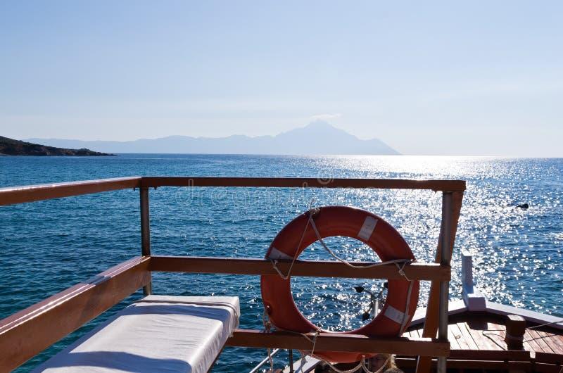 Schip, overzeese rotsen en heilige berg Athos op Achtergrond stock fotografie