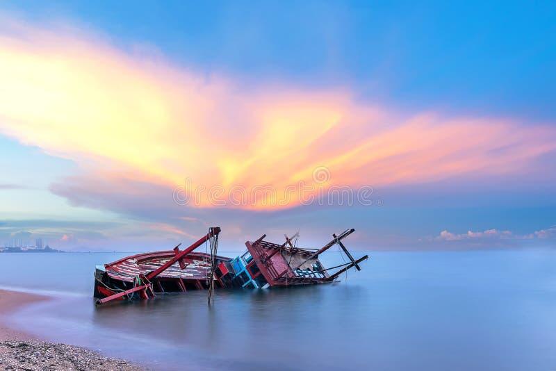Schipbreuk of gesloopte boot op strand in de zonsondergang Mooi landschap stock foto