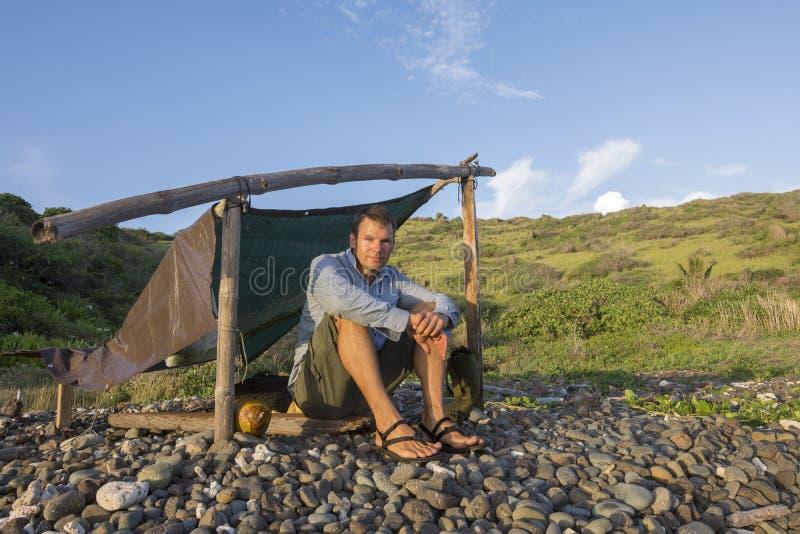 Schipbreukelingzitting bij eenvoudig kamp in ochtendlicht royalty-vrije stock afbeelding
