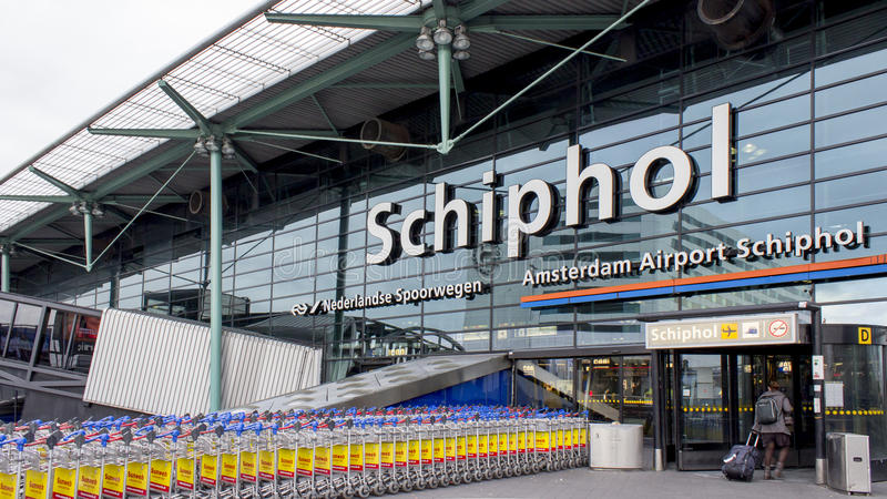 Schiphol Amsterdam airport entrance. The man walking into Schiphol Amsterdam airport with his luggage. And the long line of luggage trolley or cart stock images