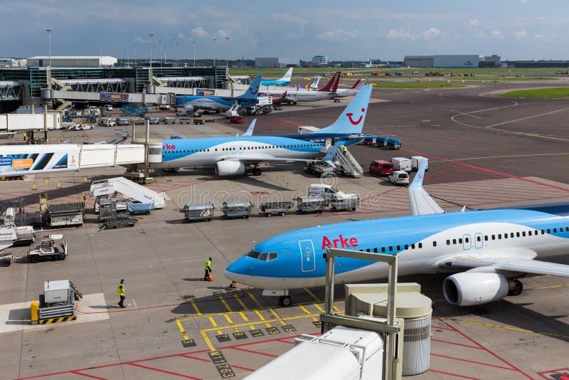 Schiphol flygplats med arbetare och avgå och ar arkivbild