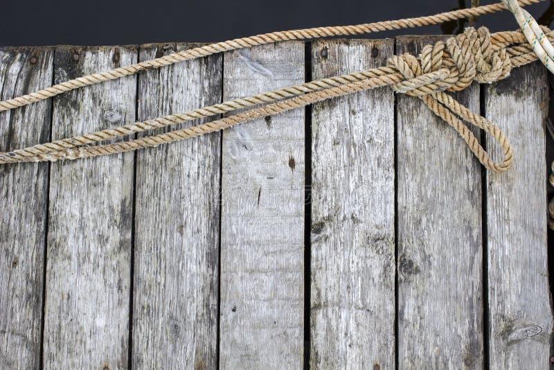 Schipkabel met mariene knoop op de oude houten pijler op de achtergrond van donkere vrdy royalty-vrije stock foto's