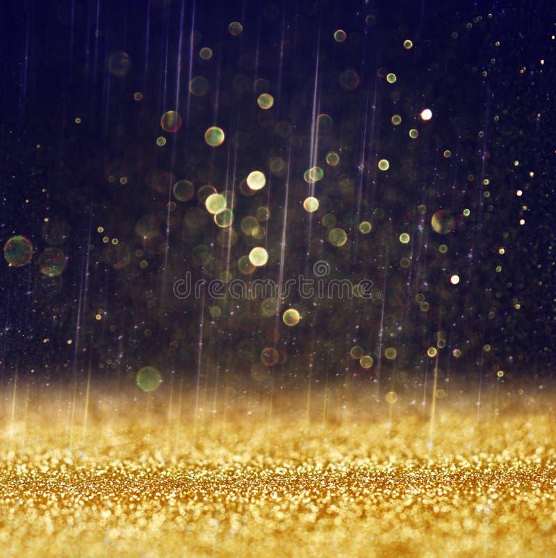 Schitter uitstekende lichtenachtergrond lichte goud en zwarte defocused stock fotografie