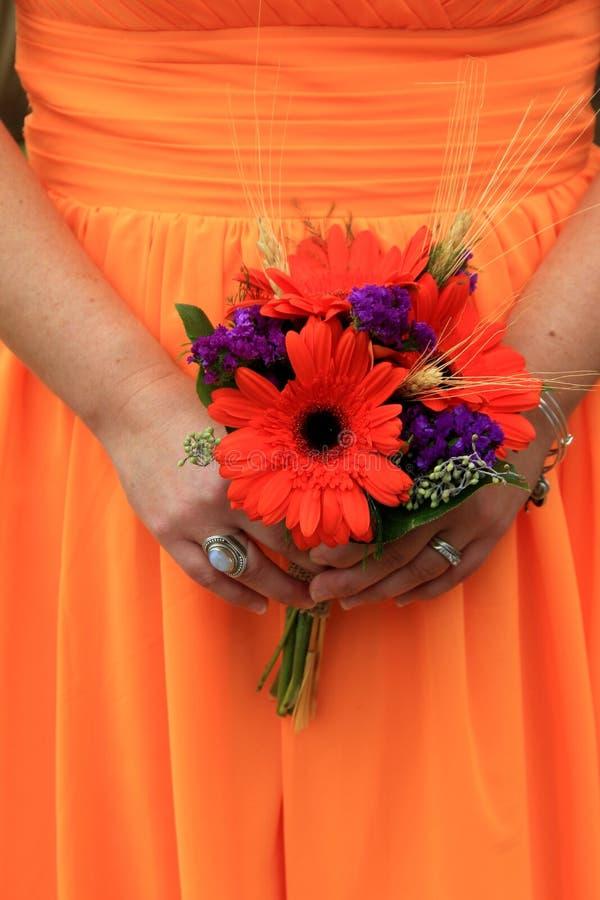 Schitterend beeld van bruidsmeisjekleding, met jonge dame in sinaasappel, die boeket houden stock foto