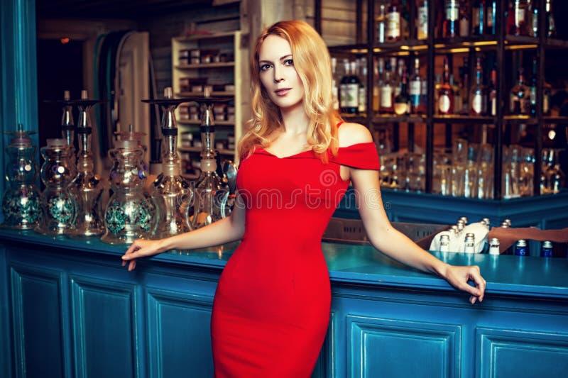 Schitterend blond meisje in manier rode kleding die bij de Waterpijp B blijven royalty-vrije stock foto