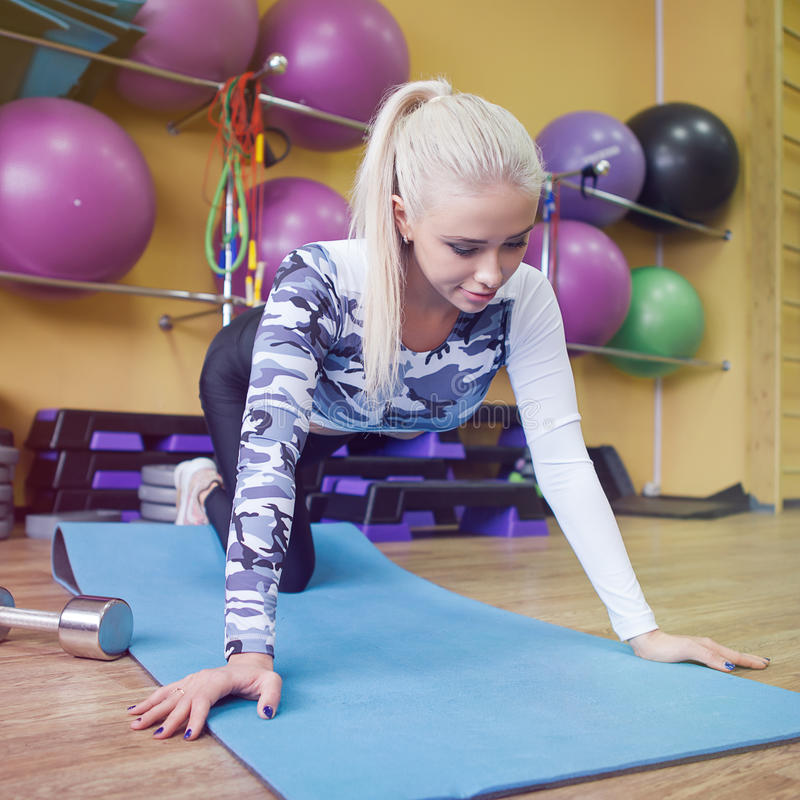 Schitterend blonde die en wat duw UPS opwarmen doen de gymnastiek stock foto