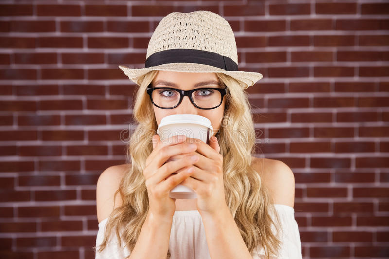 Schitterend blonde die hipster uit meeneemkop drinken royalty-vrije stock afbeelding