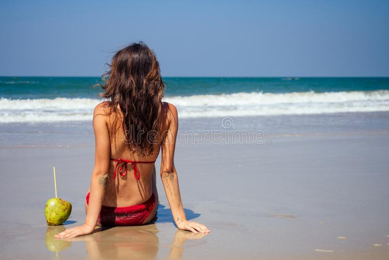 Schitterend gelooide vrouwelijke fitness big boobs model spf op de lange poten in een stijlvol modepak op zee stock foto