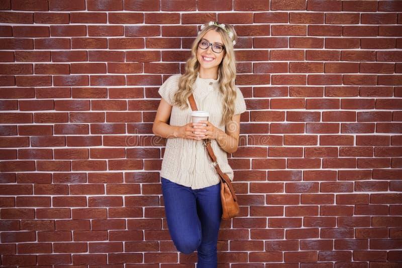Schitterend glimlachend blonde die hipster tegen rode baksteenachtergrond leunen royalty-vrije stock foto's