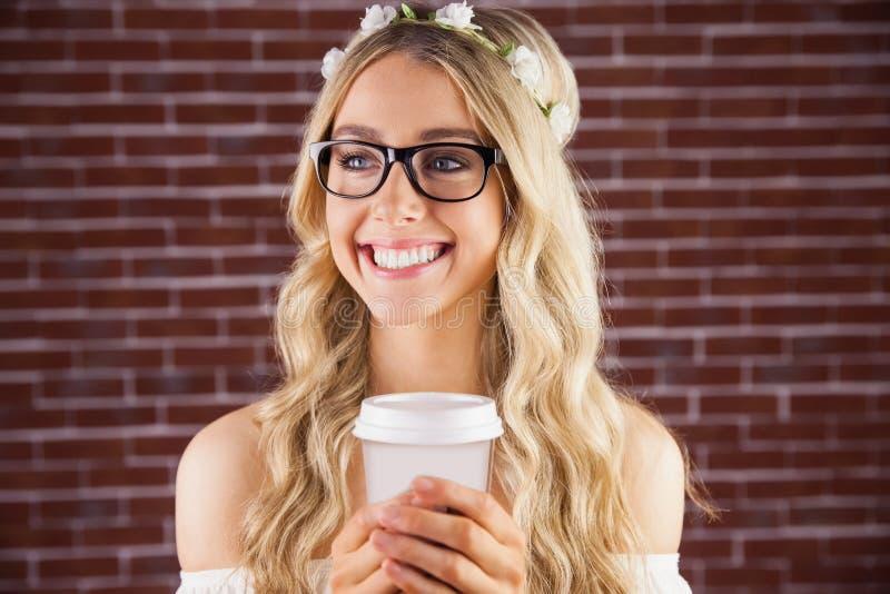 Schitterend glimlachend blonde hipster met bloemenhoofdband en koffie royalty-vrije stock afbeelding