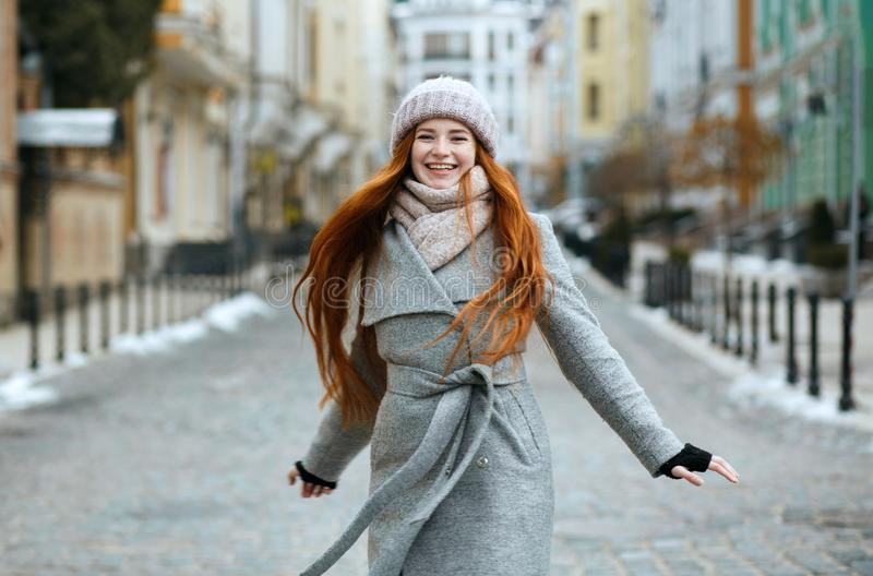 Schitterend glimlachend roodharigemeisje die de modieuze gang van de de winteruitrusting dragen royalty-vrije stock afbeeldingen