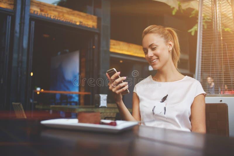 Schitterend hipstermeisje die met mooie glimlach op grappige video op celtelefoon letten tijdens lunch royalty-vrije stock fotografie