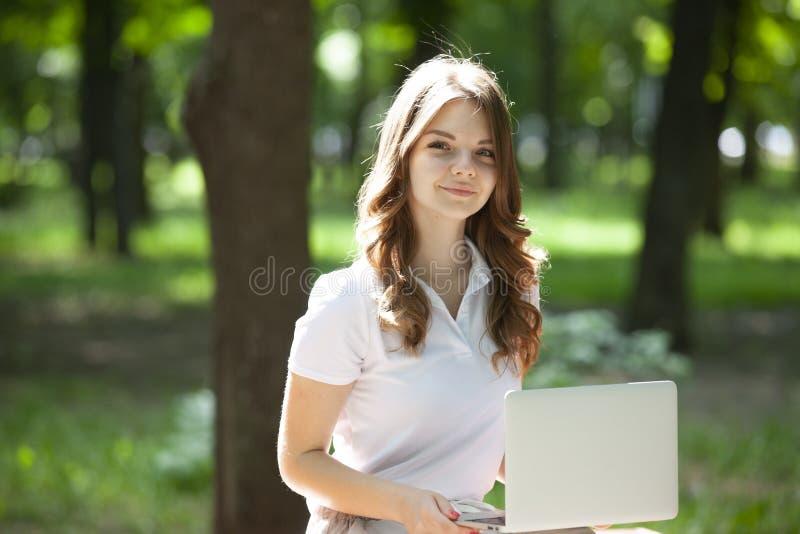 Schitterend meisje met korte blonde haargangen in het park Het leuke meisje kijkt gelukkig en glimlacht stock fotografie