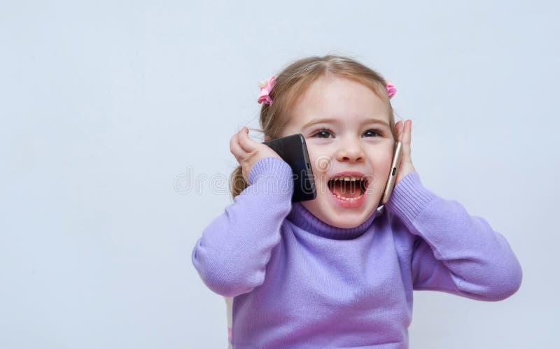 Schitterend mooi meisje ispeaks op de twee telefoons royalty-vrije stock fotografie