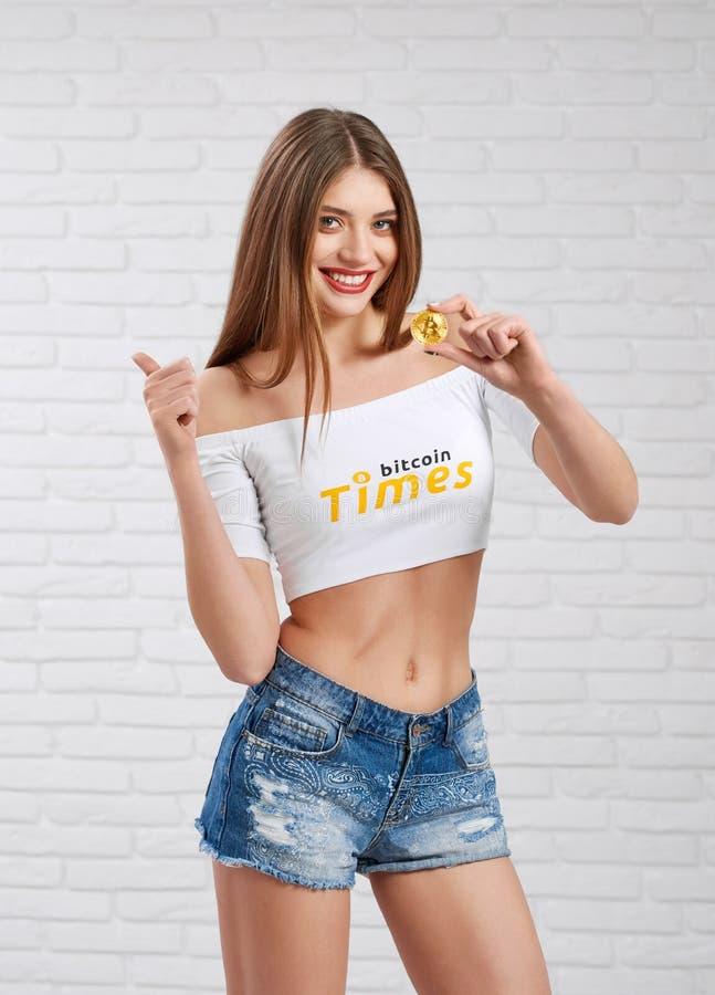 Schitterend sportief vrouwelijk model in denimborrels en witte gewassenbovenkant met bitcoinembleem die gouden bitcoin houden stock foto