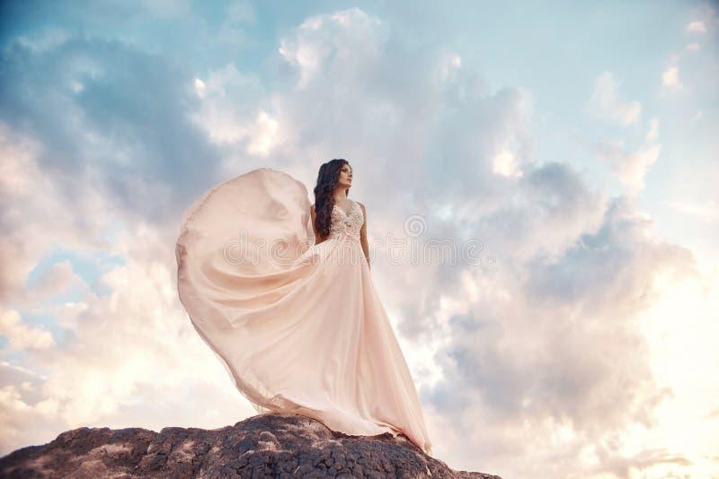 Schitterend vrouwenbrunette in de bergen bij zonsondergang en blauwe hemel met wolken De vrouw onderzoekt de afstand in een lang  royalty-vrije stock foto's