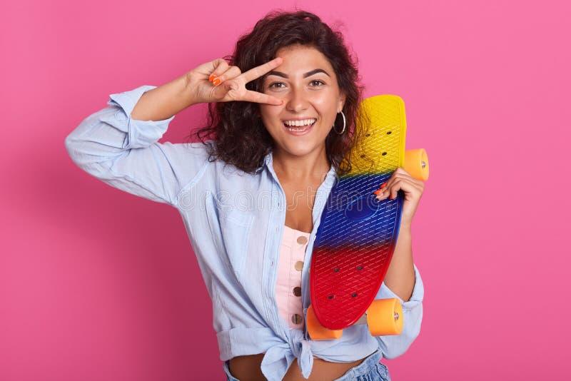 Schitterende aanbiddelijke leuke vrouw die zich over roze achtergrond in studio bevinden, lachend, zijnd in goede stemming, die k royalty-vrije stock afbeelding