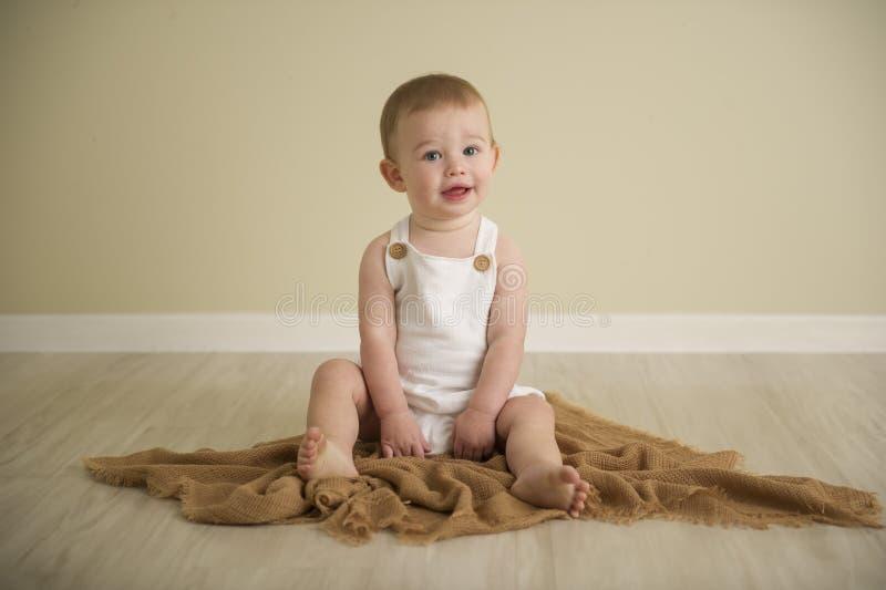 Schitterende blauwe eyed babyjongen in neutrale tonen stock afbeelding