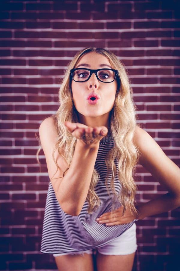 Schitterende blonde hipster blazende kus aan camera stock foto's