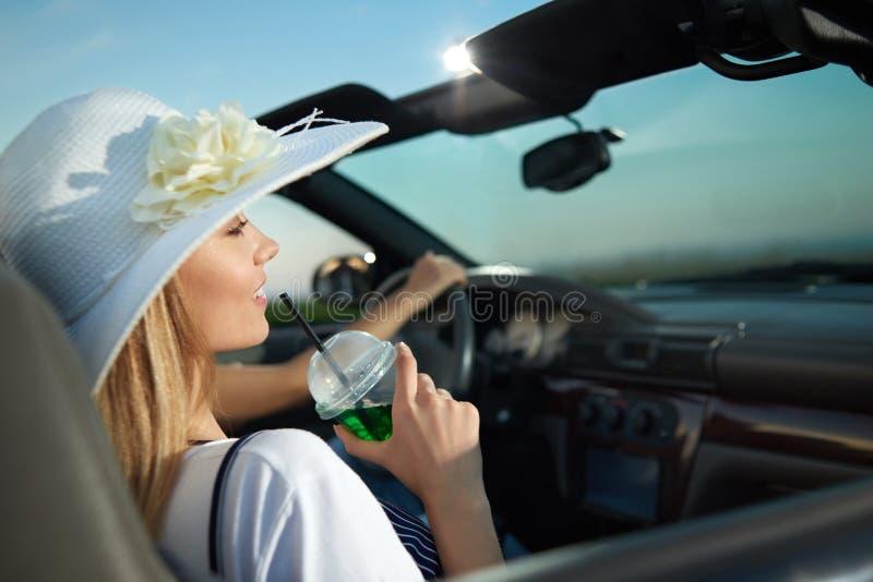 Schitterende blondezitting in luxueus cabriolet en holdingslimonadeglas royalty-vrije stock foto