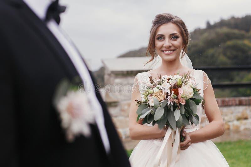 Schitterende bruid die met modern boeket modieuze bruidegom bekijken en stock fotografie