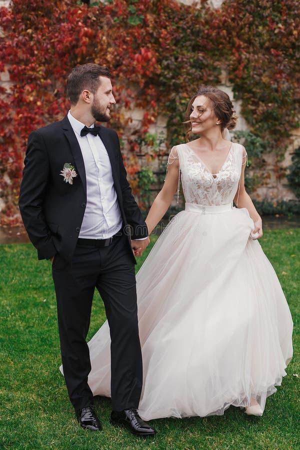Schitterende bruid en de modieuze handen van de bruidegomholding en het lopen bij wa stock foto