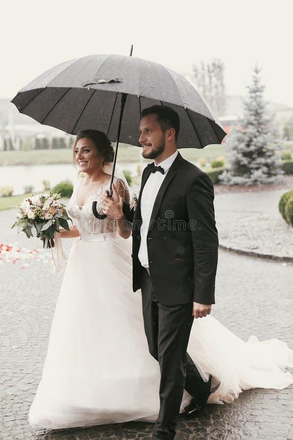Schitterende bruid en modieuze bruidegom die onder paraplu in regenachtig lopen stock afbeelding
