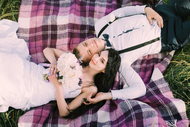 Schitterende bruid en modieuze bruidegom die op een purpere plaid liggen De ceremonie van het luxehuwelijk in een tuin stock afbeeldingen