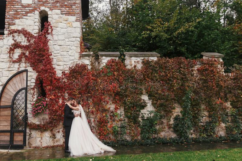 Schitterende bruid en modieuze bruidegom die zacht en koesteren glimlachen bij stock foto