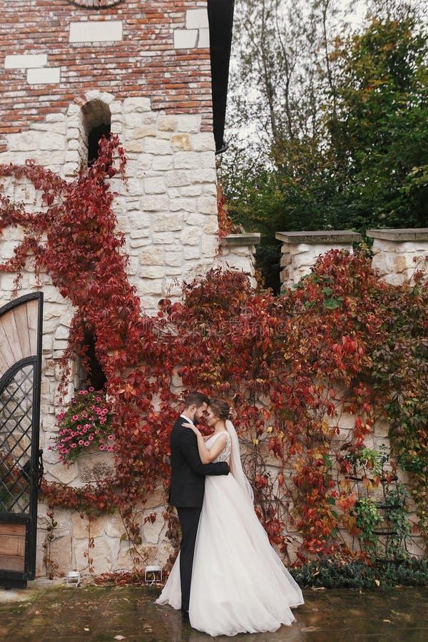 Schitterende bruid en modieuze bruidegom die zacht en koesteren glimlachen bij royalty-vrije stock afbeelding