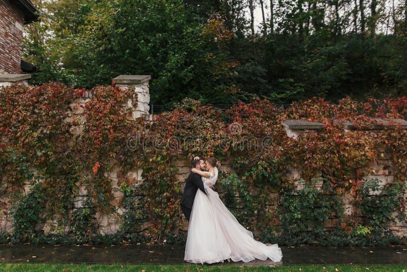 Schitterende bruid en modieuze bruidegom die zacht en koesteren glimlachen bij stock fotografie
