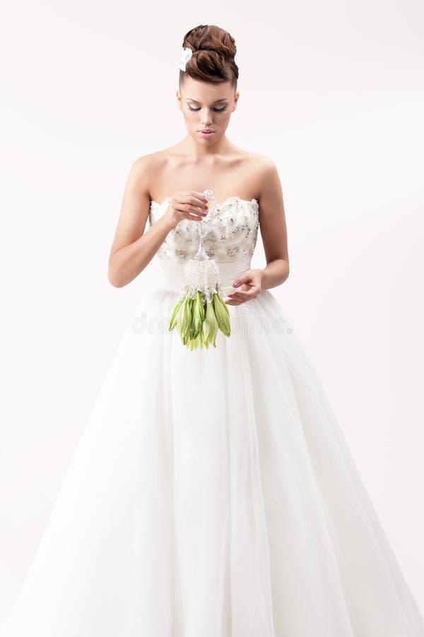 Schitterende bruid in lange witte luxekleding stock foto