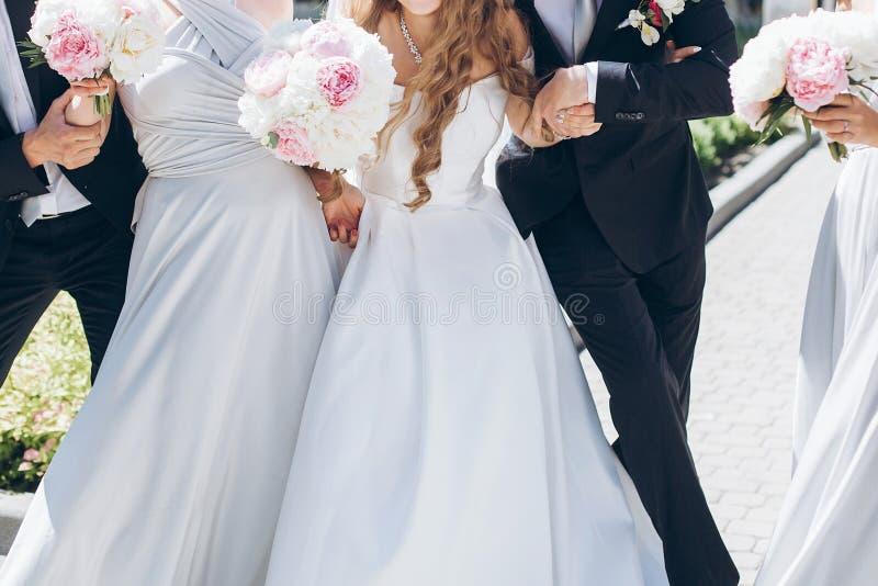 Schitterende bruid met pioenboeket en het modieuze bruidegom stellen in su stock foto