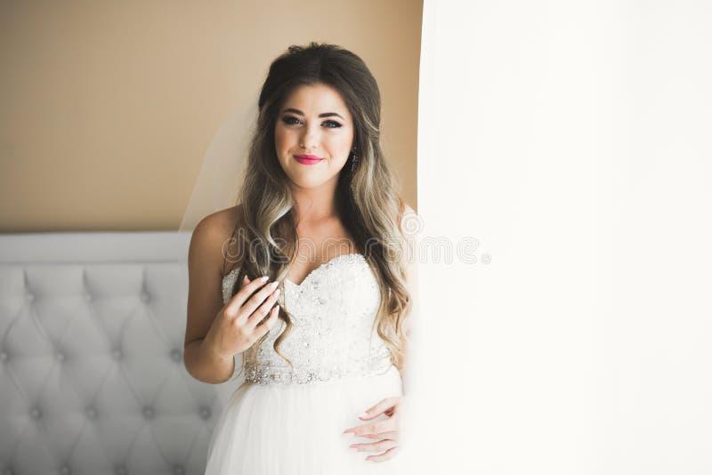 Schitterende bruid in robe die en voor het gezicht van de huwelijksceremonie in een ruimte stellen voorbereidingen treffen stock afbeeldingen