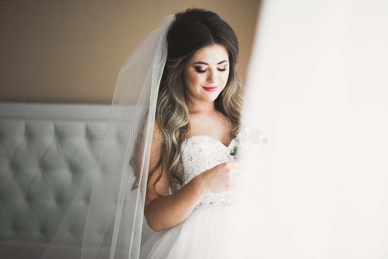 Schitterende bruid in robe die en voor het gezicht van de huwelijksceremonie in een ruimte stellen voorbereidingen treffen royalty-vrije stock foto