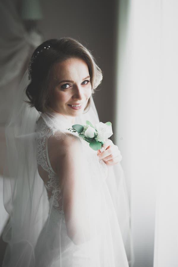 Schitterende bruid in robe die en voor het gezicht van de huwelijksceremonie in een ruimte stellen voorbereidingen treffen stock foto's