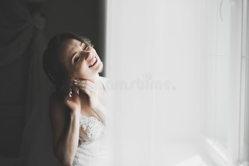 Schitterende bruid in robe die en voor het gezicht van de huwelijksceremonie in een ruimte stellen voorbereidingen treffen stock fotografie