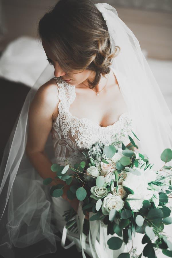 Schitterende bruid in robe die en voor het gezicht van de huwelijksceremonie in een ruimte stellen voorbereidingen treffen royalty-vrije stock afbeeldingen