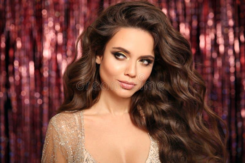 Schitterende brunette met Healthy wavy hair Glamor Makeup Fashion Beauty Girl met carnavalsmasker Geïsoleerd op een fel hokje royalty-vrije stock afbeeldingen