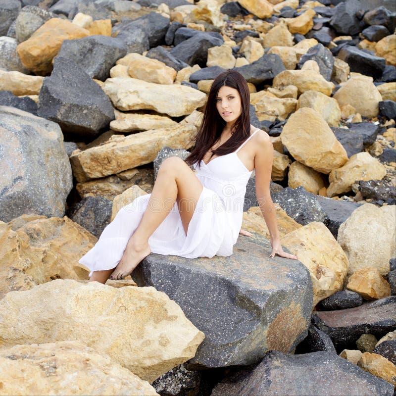 Schitterende dame met witte kledings stellende zitting bij rotsen glimlachen die camera middelgroot schot kijken stock afbeeldingen