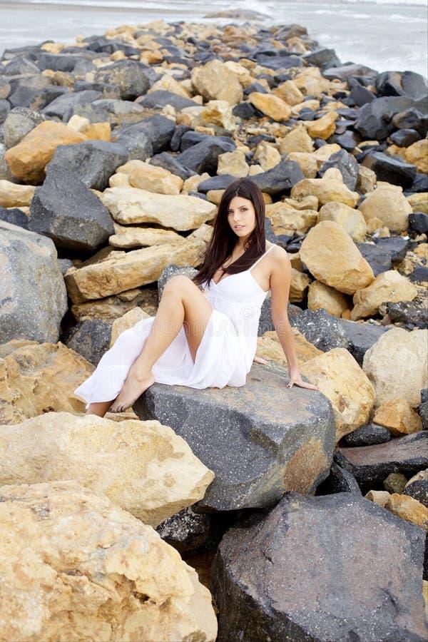 Schitterende dame met witte kledings stellende zitting bij rotsen glimlachen die camera wijd geschoten kijken royalty-vrije stock foto's