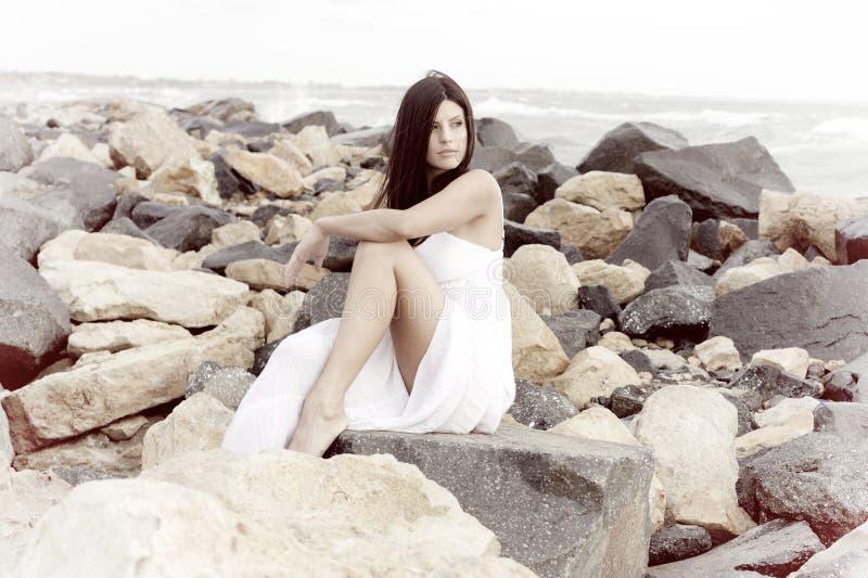 Schitterende dame met witte kledings stellende zitting bij rotsen glimlachen die de oceaan gelukkige retro stijl kijken stock foto