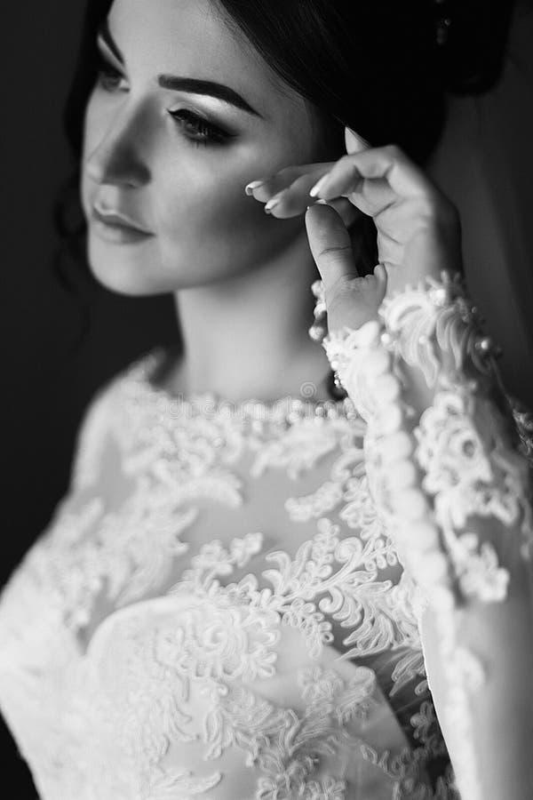 Schitterende donkerbruine bruid die binnenhotelruimte stellen vóór ceremonie stock fotografie