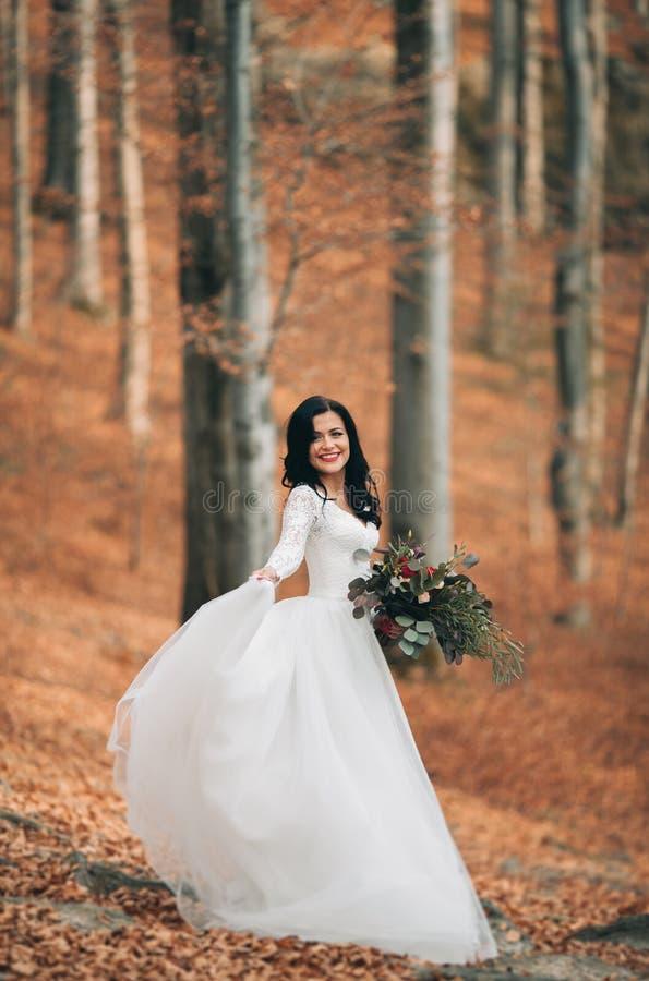 Schitterende donkerbruine bruid in het elegante het boeket van de kledingsholding stellen dichtbij bos en meer royalty-vrije stock afbeelding
