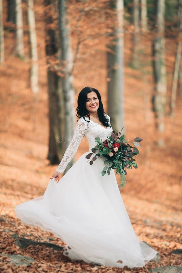 Schitterende donkerbruine bruid in het elegante het boeket van de kledingsholding stellen dichtbij bos en meer stock foto's