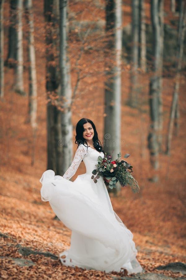 Schitterende donkerbruine bruid in het elegante het boeket van de kledingsholding stellen dichtbij bos en meer royalty-vrije stock fotografie